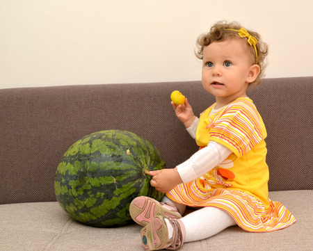 The one-year-old girl sits on a sofa and holds with a hand watermelon Stock Photo