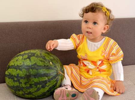 The little girl sits on a sofa and shows a hand on watermelon Stock Photo