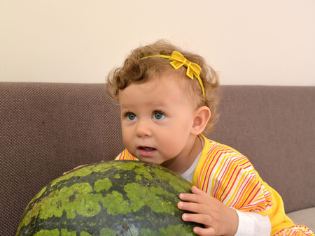 The little girl embraces hands big watermelon Stock Photo