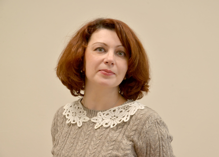 The woman in a gray sweater with a lacy collar. A portrait on a light background Stock Photo