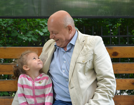 The elderly man and the little girl with a smile look at each other Stock Photo