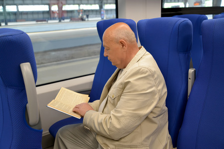 The elderly man reads the book in the electric train car