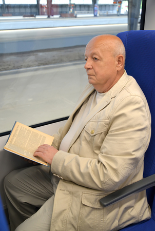 The thoughtful elderly man reads the book in the electric train car