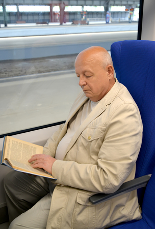 The man of a retirement age reads the book in the electric train car