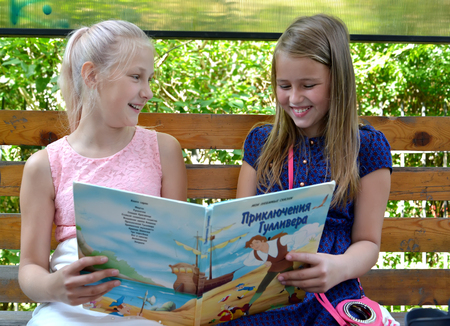 KALININGRAD, RUSSIA - JUNE 28, 2018: Cheerful girls girlfriends discuss the book on a bench. The Russian text - Gulliver's Travels Éditoriale