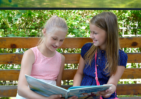 KALININGRAD, RUSSIA - JUNE 28, 2018: Two cheerful girls read the book on a bench. The Russian text - Gulliver's Travels