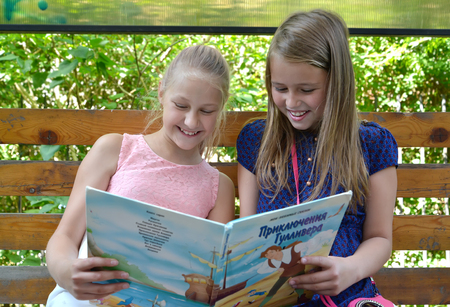 KALININGRAD, RUSSIA - JUNE 28, 2018: Two girls girlfriends with a smile consider the book on a bench. The Russian text - Gulliver's Travels Banque d'images - 107474052