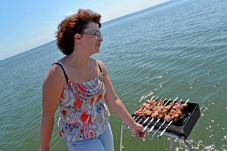 The woman prepares a shish kebab on the brazier fixed on a yacht hand-rail. Kaliningrad region Stock Photo