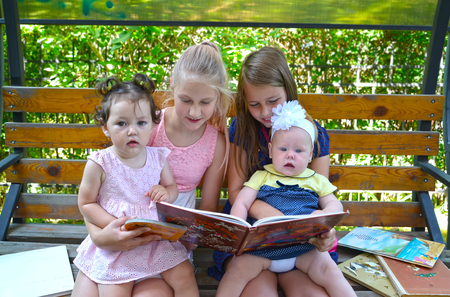 KALININGRAD, RUSSIA - JUNE 28, 2018: Children with interest consider the book on a bench in the park