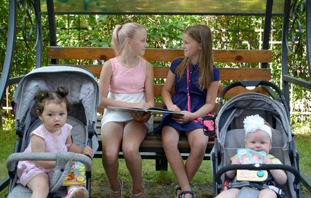 KALININGRAD, RUSSIA - JUNE 28, 2018: Girls with little sisters sit on a bench in the park with the book in hands Banque d'images - 107474185