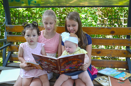 KALININGRAD, RUSSIA - JUNE 28, 2018: Girls schoolgirls with little sisters consider the book on a bench in the park