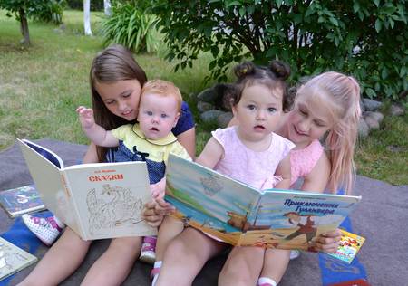 KALININGRAD, RUSSIA - JUNE 28, 2018: Girls with little sisters read books, sitting on a grass in a garden