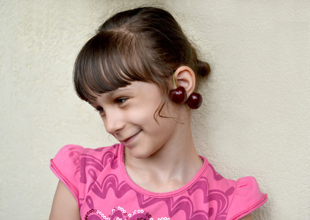 The seven-year-old girl with sweet cherry berries as earrings on ears. Portrait Imagens