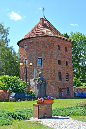 BRANIEWO, POLAND - JUNE 07, 2016: A monument to blessed Regina Protmann (1552-1613) against the background of a medieval city tower