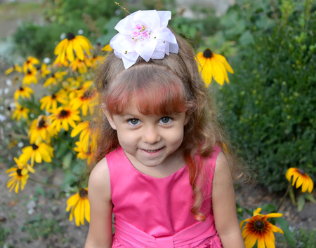 Portrait of the little girl against the background of the blossoming coneflowers
