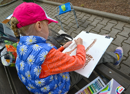 KALININGRAD, RUSSIA - JUNE 06, 2018: The girl draws a giraffe. A childrens open-air in a zoo