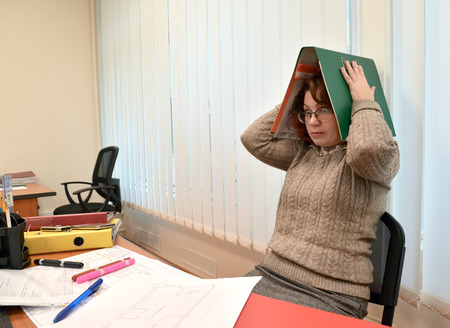 The female manager with horror looks and holds the folder with documents on the head Stock Photo