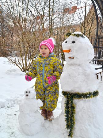 The joyful three-year-old girl costs near a snowman