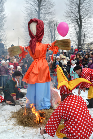KALININGRAD, RUSSIA - FEBRUARY 18, 2018: Buffoons with torches set fire to an effigy. The celebration of Maslenitsa in the park