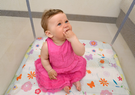 The eight-months girl cries, having thrust fingers into a mouth