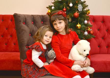 Two girls with toys in hands sit against the background of a New Year tree