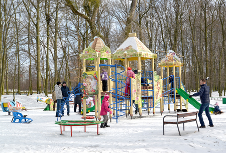 Adults play with children at the playground in the winter park. Kaliningrad Banque d'images - 111641991