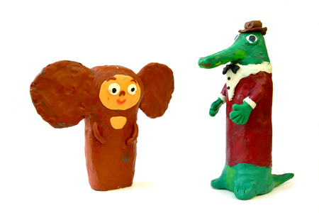 Plasticine figures the Cheburashka and Genas Crocodile on a white background. Childrens creativity