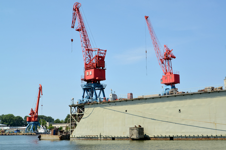 Port cranes and ship dock in port. City Svetlyj, Kaliningrad region Imagens