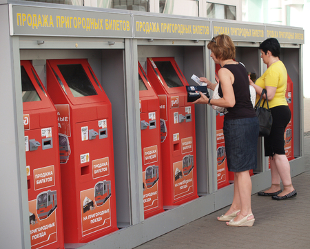 MOSCOW, RUSSIA - JULY 02, 2011: People buy suburban tickets in automatic machines at the Belarusian station. The Russian text - sale of suburban tickets