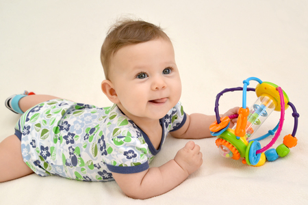 The amusing baby holds a toy lying on a stomach