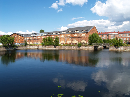 ST. PETERSBURG, RUSSIA - JULY 15, 2015: A view of warehouse buildings and a pond in summer day. Island New Holland