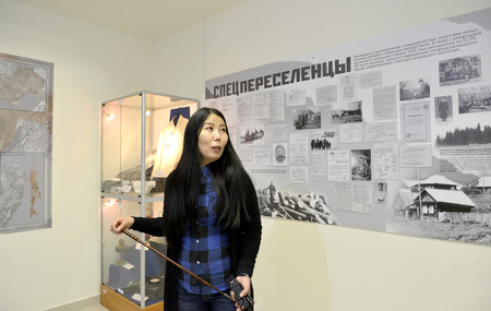 ELISTA, RUSSIA - APRIL 22, 2017: The girl guide in museum department Deportation of the Kalmyk people. National museum of Kalmykia of N.N. Palmov. The Russian text - Special immigrants