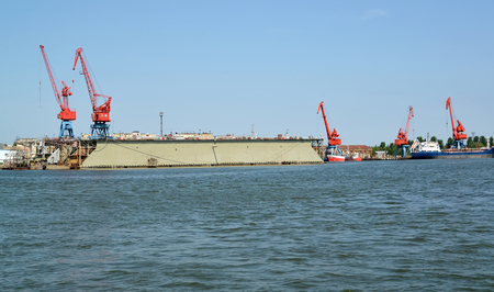 Portal cranes and floating ship dock from the sea. Kaliningrad region