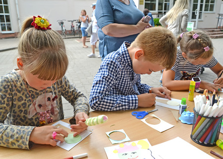 KALININGRAD, RUSSIA - JULY 08, 2018: Children are engaged in applique from color paper. Children's master class in the open air Editorial