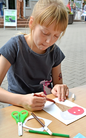 KALININGRAD, RUSSIA - JULY 08, 2018: The girl paints with a felt-tip pen a paper hand-made article. Childrens master class in the open air