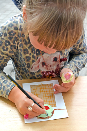 KALININGRAD, RUSSIA - JULY 08, 2018: The girl paints paper applique. Childrens master class in the open air