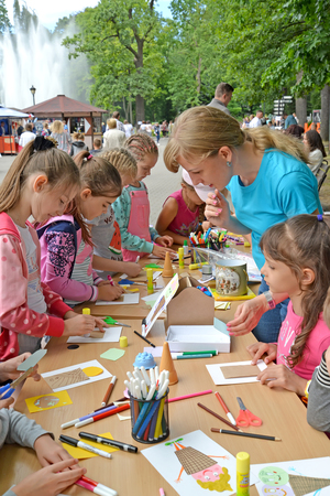 KALININGRAD, RUSSIA - JULY 08, 2018: The teacher is engaged with children in paper applique on a master class in the park Editorial