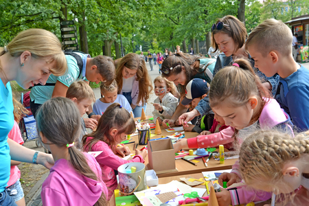 KALININGRAD, RUSSIA - JULY 08, 2018: Joint class of parents and children in production of paper applique. A childrens master class on in the open air Редакционное