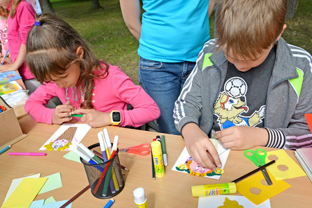 KALININGRAD, RUSSIA - JULY 08, 2018: The boy and the girl do applique of color paper. Childrens master class in the open air