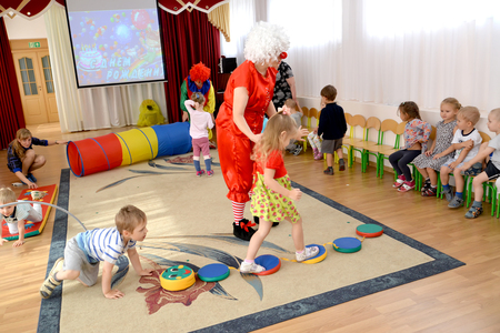 KALININGRAD, RUSSIA - SEPTEMBER 14, 2017: The clown-animator conducts the child on a touch path. Cheerful relay in younger group