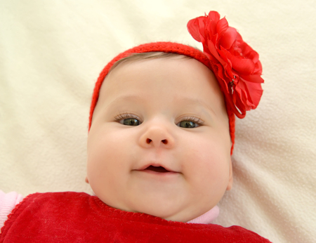 Portrait of the six-months girl with a red flower on the head