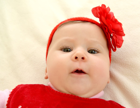 Portrait of the surprised baby with a red flower on the head