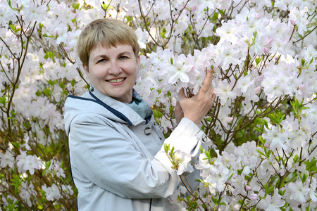 The fifty-year-old woman against the background of the blossoming Shlippenbakh's rhododendron Фото со стока