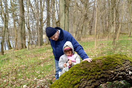 The grandfather and the granddaughter consider the first spring flowers in the forest