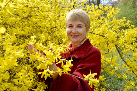Portrait of the fifty-year-old woman among yellow colors of a forsaytiya