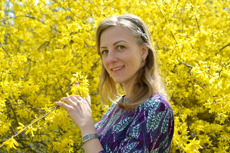 Portrait of the young woman against the background of yellow colors of a  forsythia