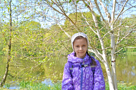The seven-year-old girl against the background of the blossoming trees in the park. Spring