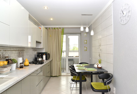 The modern light kitchen with the built-in furniture. Interior