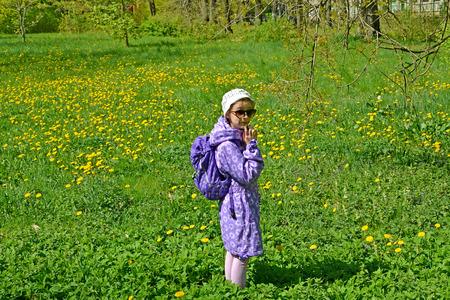 The seven-year-old girl costs among the blossoming dandelions in the park. Spring