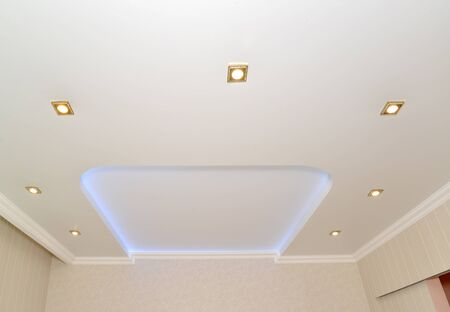 Fragment of an opaque stretch ceiling with the central design and dot lamps Stok Fotoğraf